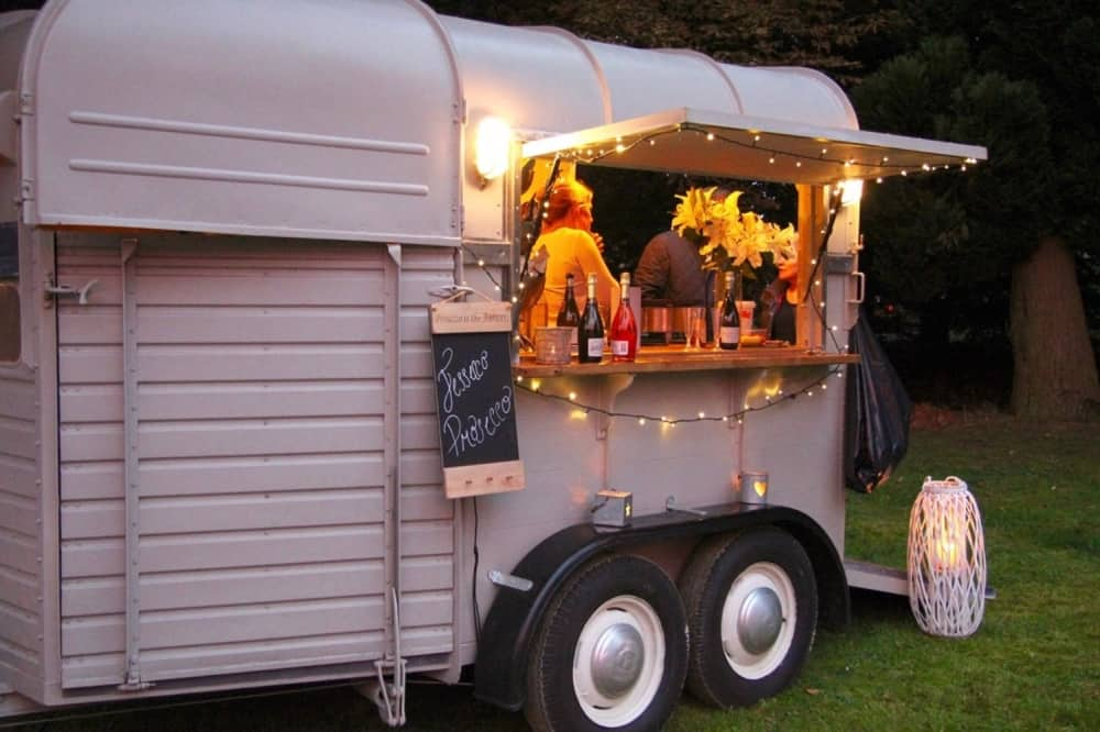 Conveted Horse box serving prosecco and pancakes fairy lights