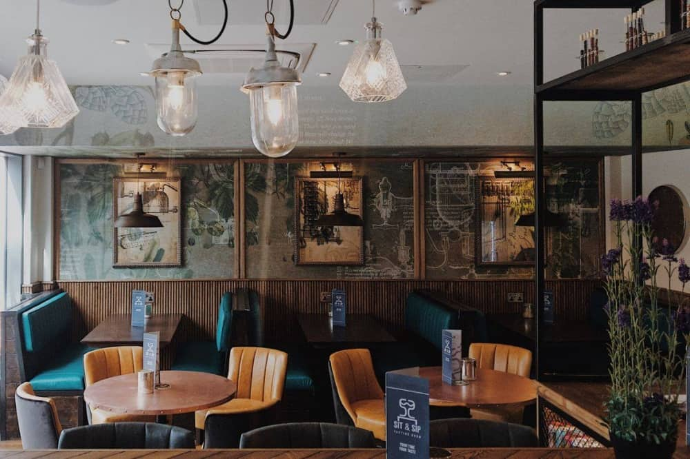 Sit and Sip Wokingham white retro mismatched hanging lights leather seating industrial lighting and marbled walls