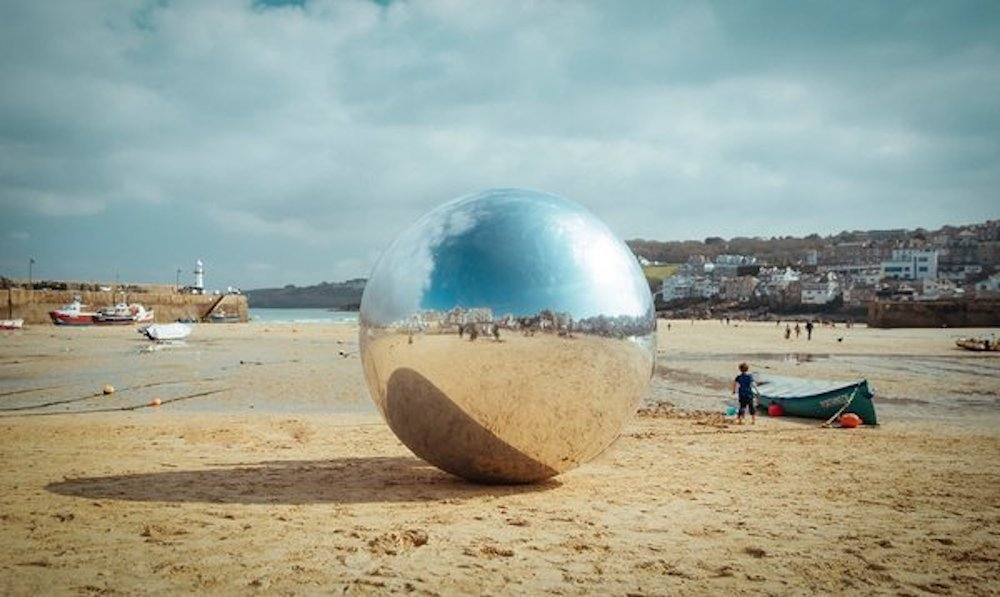St ives beach Cornwall giant metal ball on sand