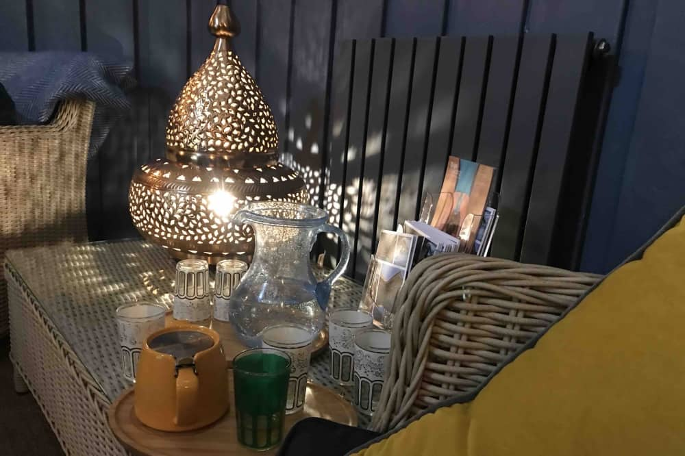 Thames Lido Spa Relaxation Room morroccan lamp and tea light water bottles and rattan furniture