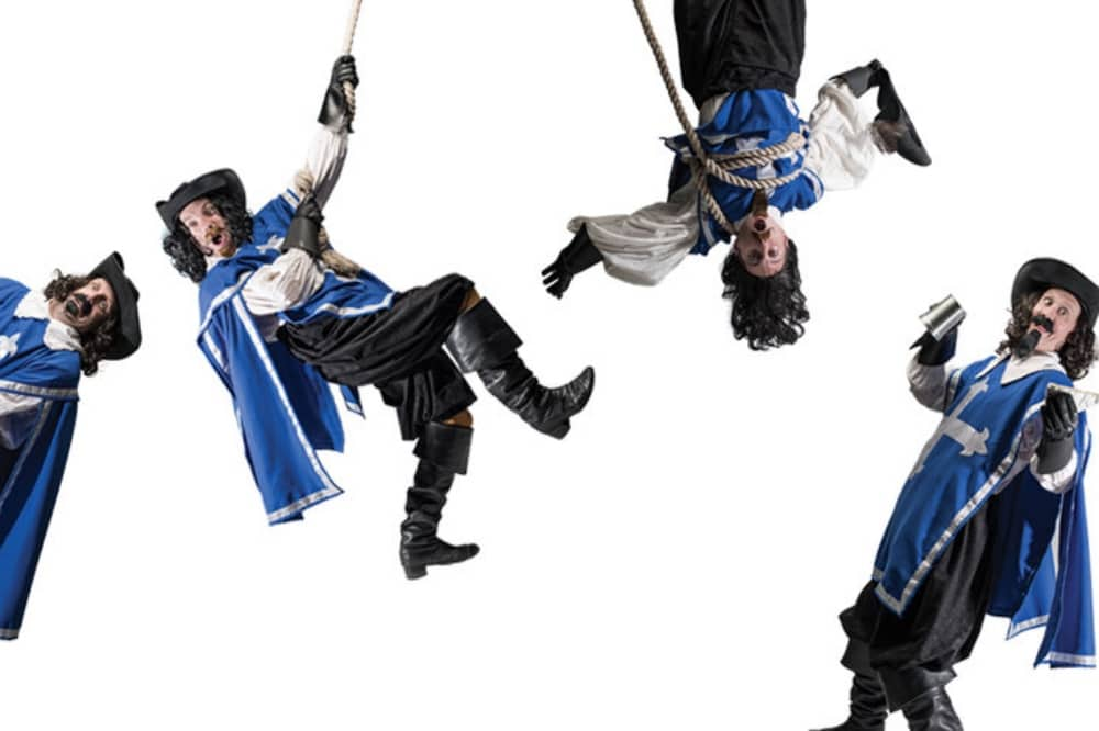 Three musketeers blue tunics hanging from rope, fighting with a sword and drinking with tankard