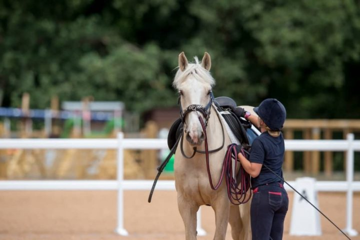 Wellington Riding Berkshire Hampshire girl checking saddle and girth of pony in menage