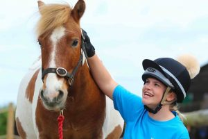 Wellington Riding Berkshire Hampshire girl in riding hat and blue t shirt fussing chestnut pony