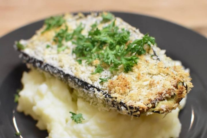 Aubergine and vegan cheese schnitzel recipe on black plate