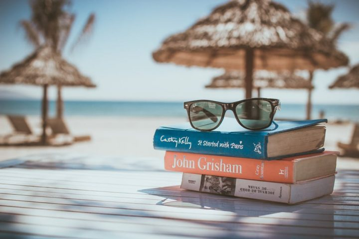 books and sunglasses on a table beach sandy beach blue sea raffia sun parasol