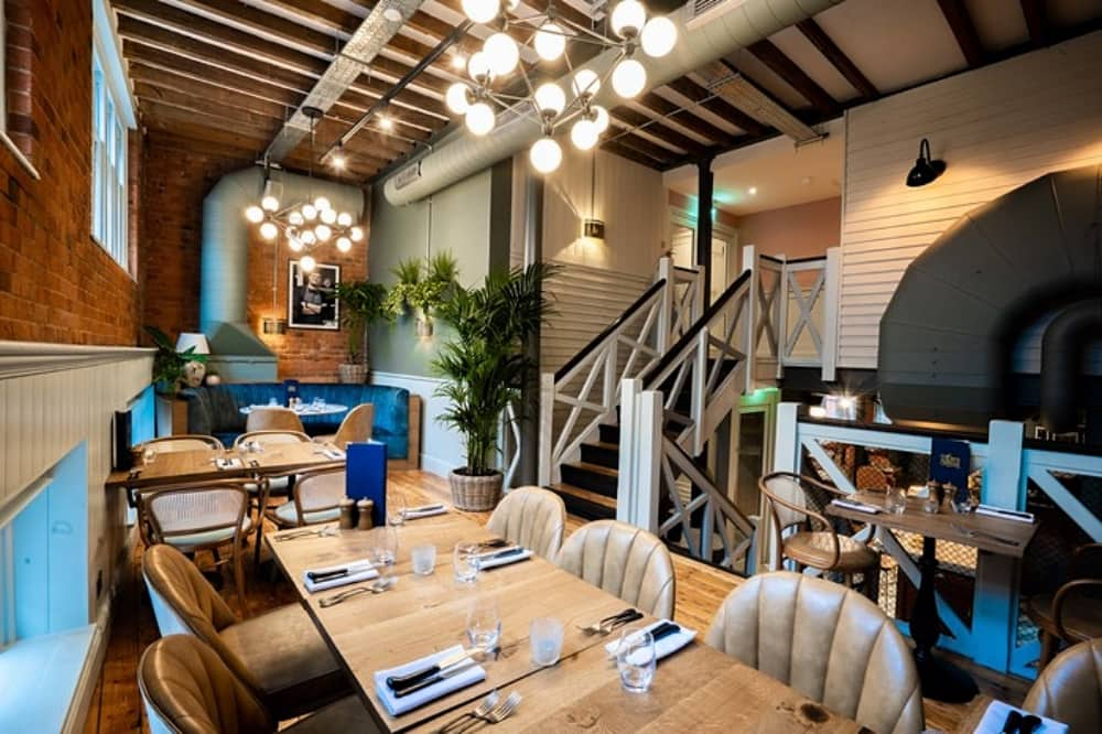 The Corn Stores Reading Restaurant Rarebreed Dining Group mid century interiors leathher chair wood tables exposed beams and mid century globe light