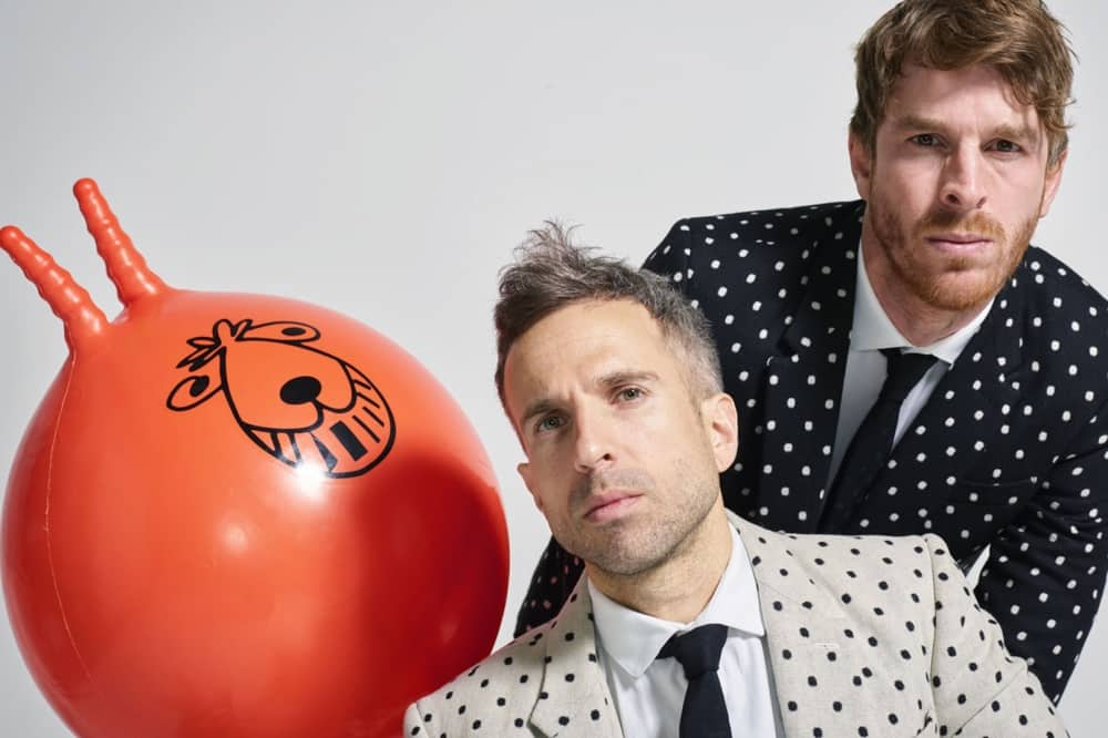 two comedians in polka dot suits with a space hopper