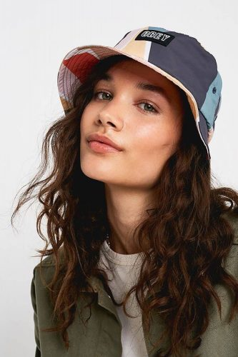 Female model brunette long hair khaki jaccket and urban outfitters bucket hat