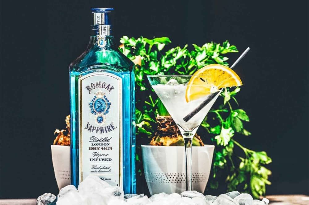Bombay Sapphire blue bottle cocktail glass with lemon slice ice tonic herbs