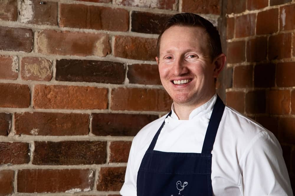 L'ortolan Executive chef Tom Clarke in navy apron brick wall