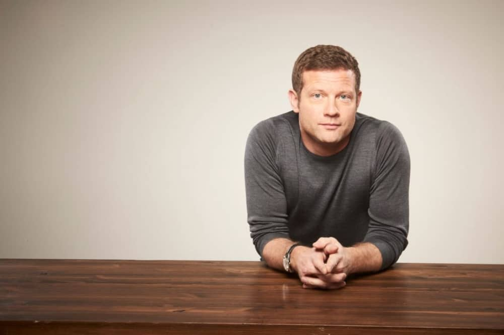 Tv presenter and DJ Dermot O'Leary in jumper leaning on wooden counter