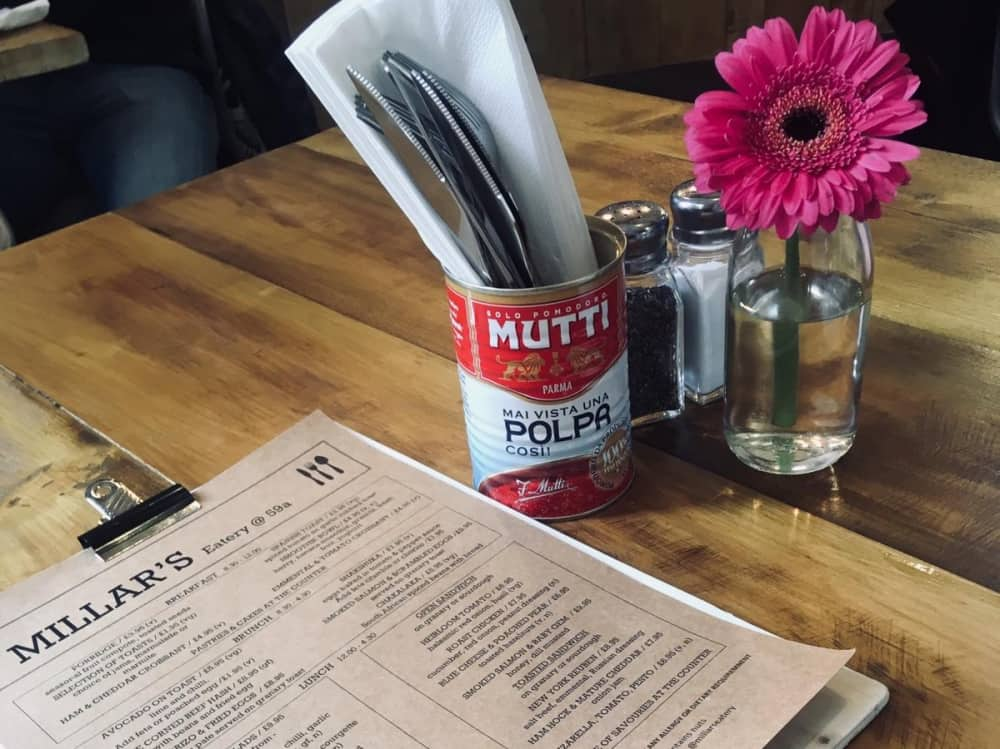 Millar's Eatery Windsor wooden table tin can with cutlery PINK GERBRA in milk bottle and menu