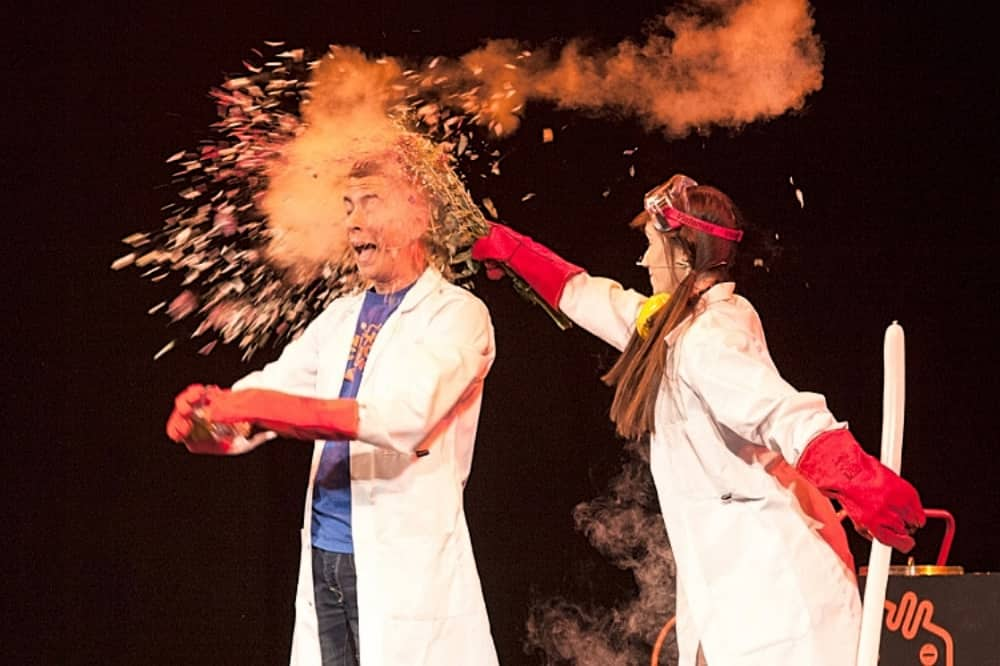 Ministry of Science woman and man in lab coats and safety goggles doing explosive experiment on stage