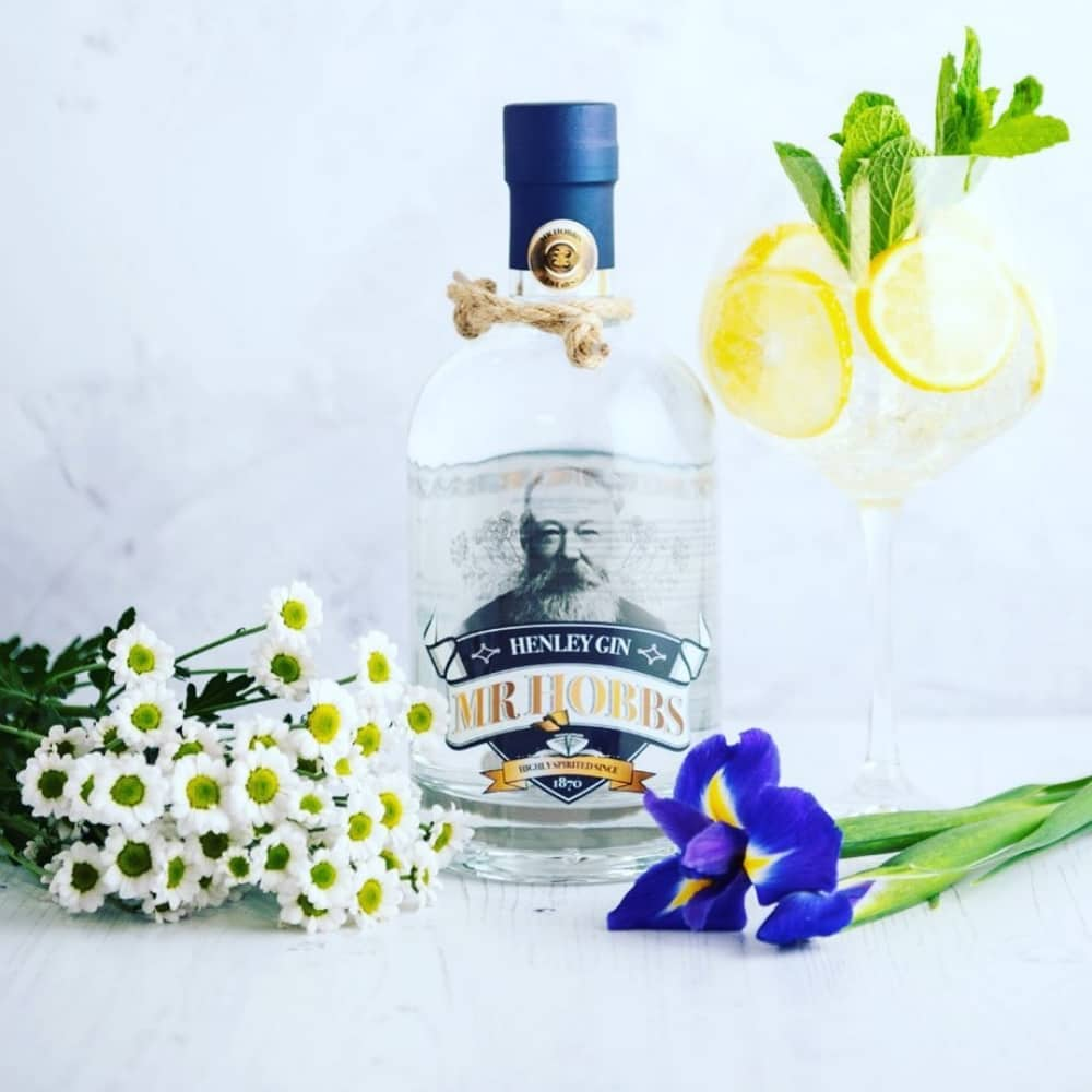 Mr Hobbs Henley gin bottle with bluue cap daisies irises and gin balloon glass with lemon and ice