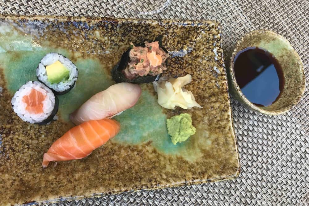 Sushhi on rustic rectangular plate and small bowl with dipping soy