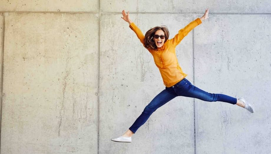 Woman jumping for joy by concrete wall