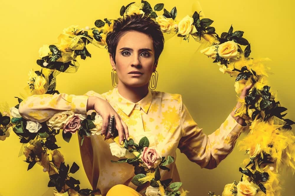 comedian Jen Brister wearing yellow sat under a yellow flower hoop