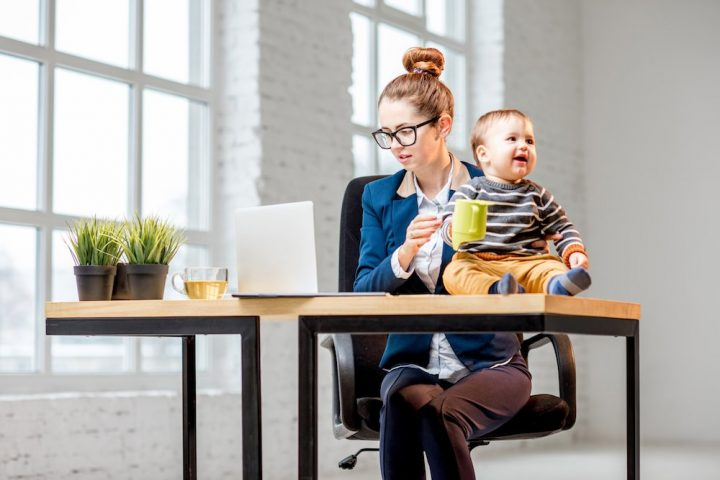 woman weariing glasses and suit at desk with laptop juggling a baby