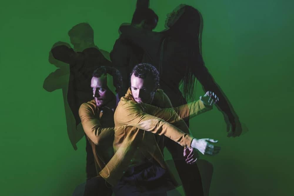 BalletBoyz The/ Us two danccers beige jacket green backgroujnd shadows