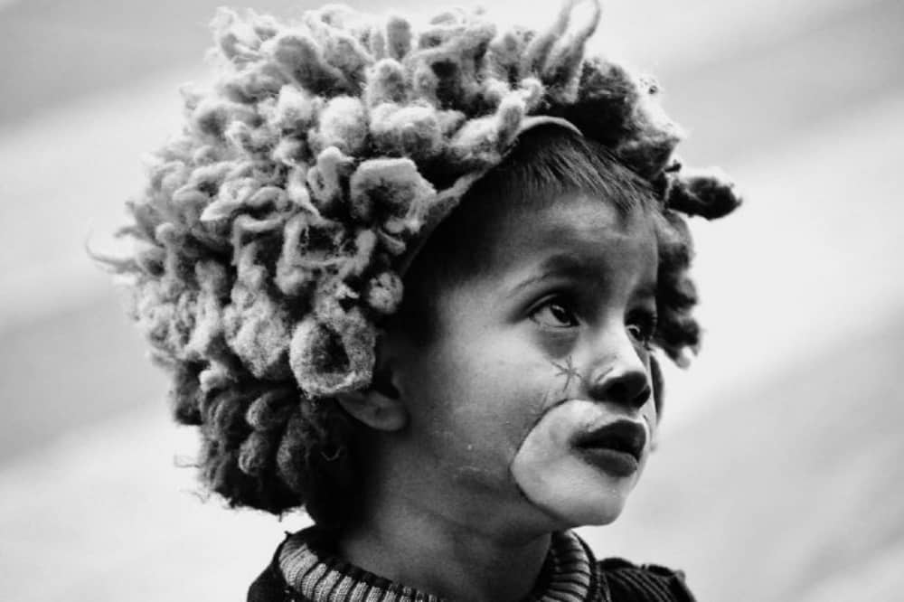 black and white photo little by with dreadlocked hair and painted face