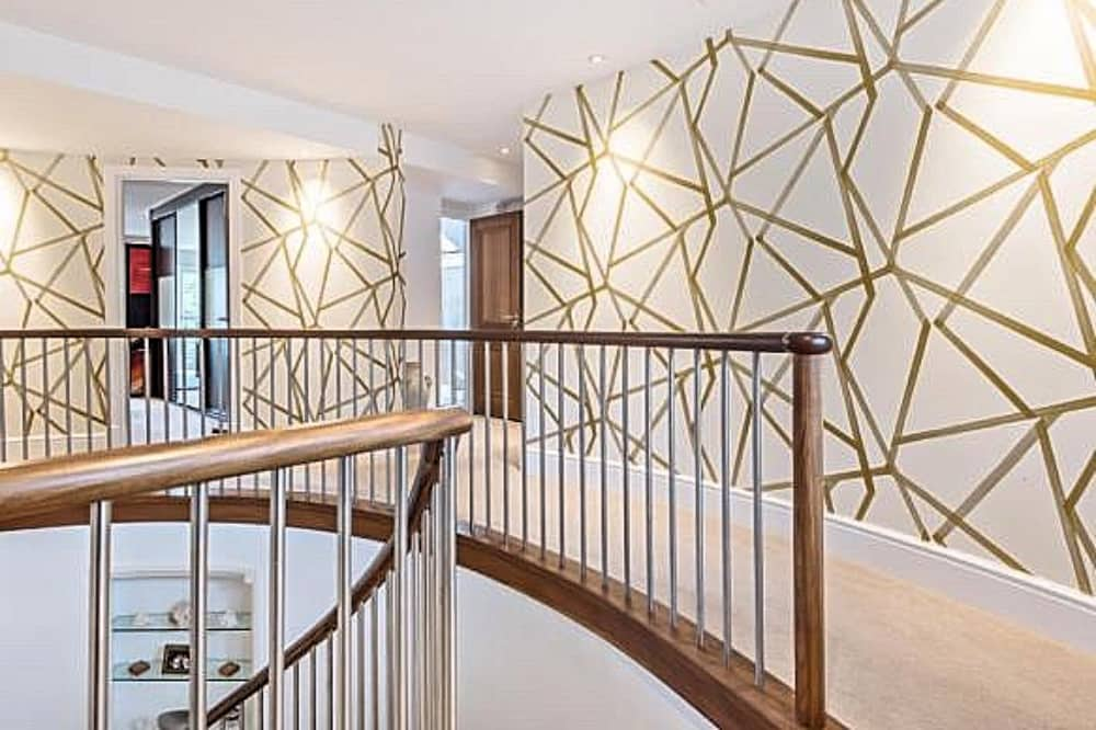 gold and white geometric wallpaper landgin Garden House Hurst Berkshire