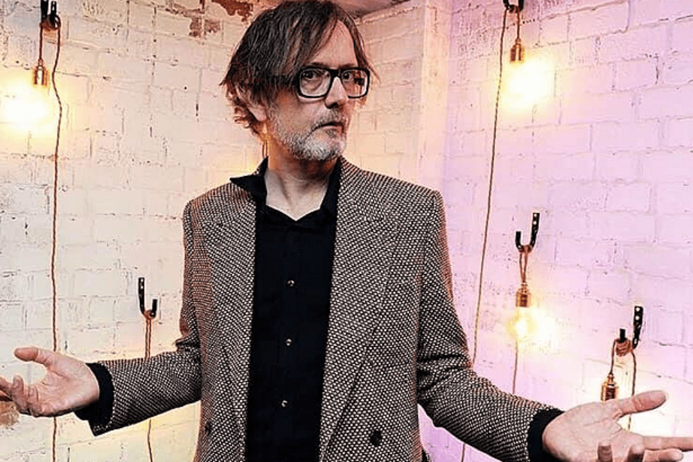 Singer Songwriter Jarvis Cocker tweed jacket black speccs