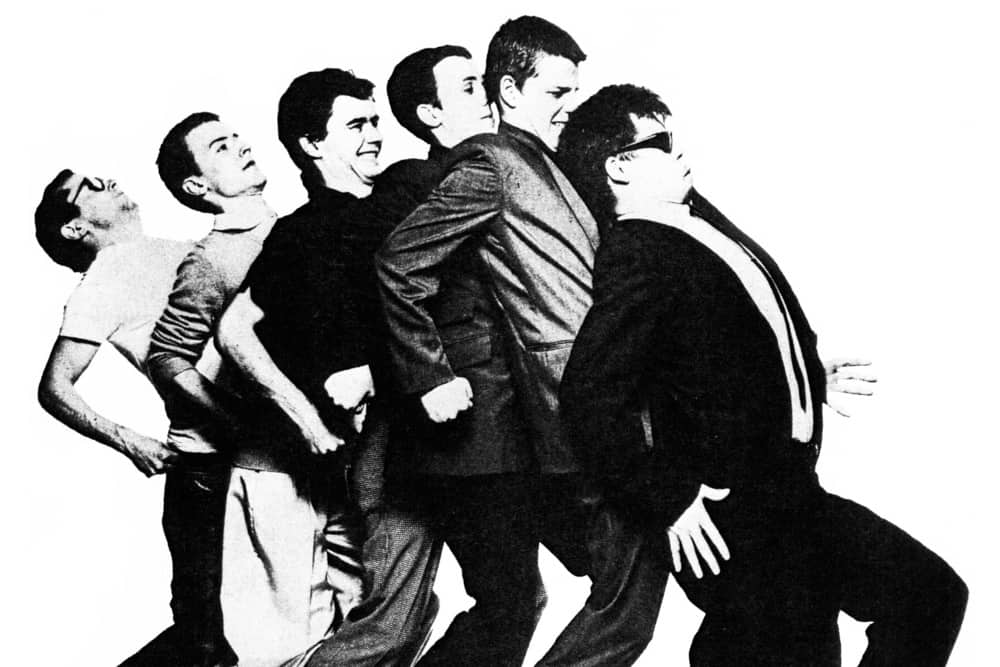 Madness black and white ska band leaning back into each other