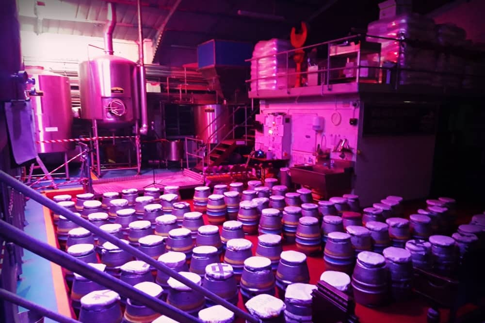 Brewery Comedy Windsor and Eton Brewery pink lighting beer barrel stools and takns of beer behind stage