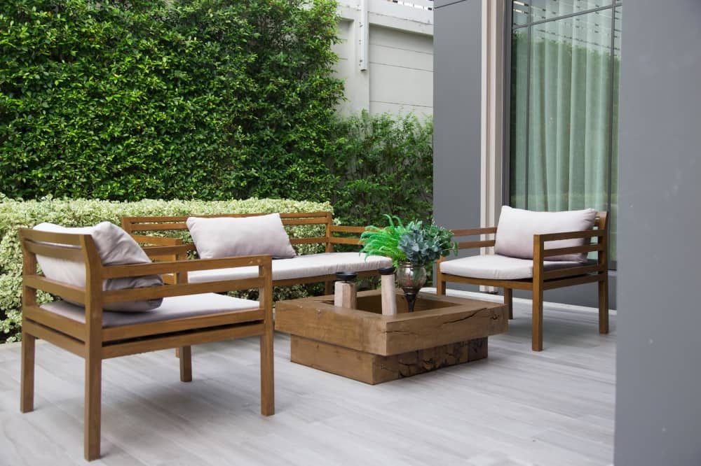Wooden contemporary garden furniture cream cushions deck and green hedge