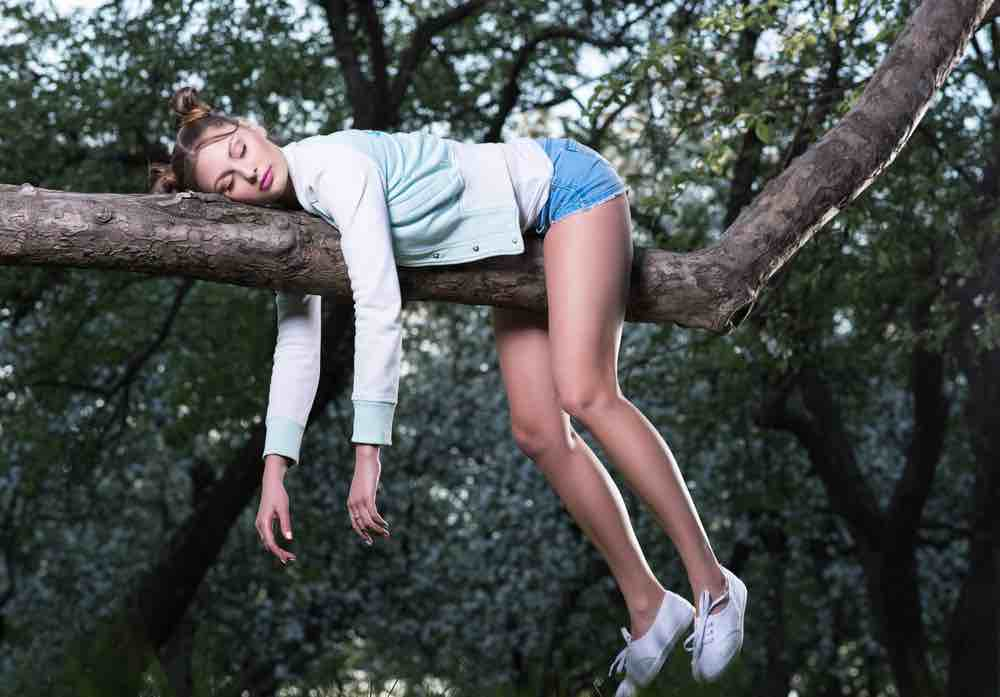 Girl sleeping on a tree branch