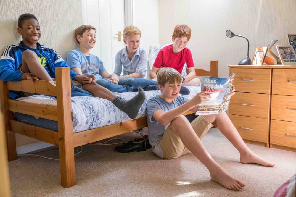 HORRIS BOYS PREP SCHOOL BOARDING HOUSE BOYS SAT ON BED READING MAGAZINE