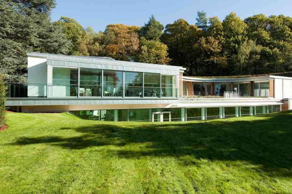 Ascot Coworth Park spa curved glass and timer building living roof set into the hILL
