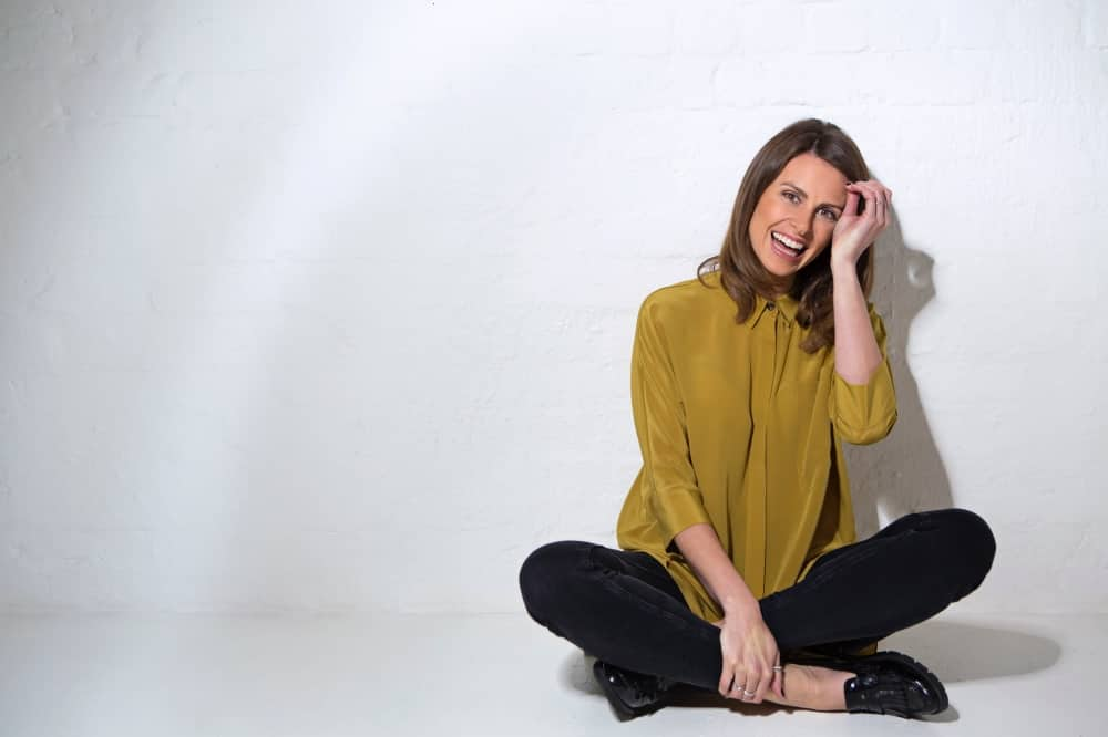 Comedian Ellie Taylor brunette sat crossed legs in mustard shirt and jeans