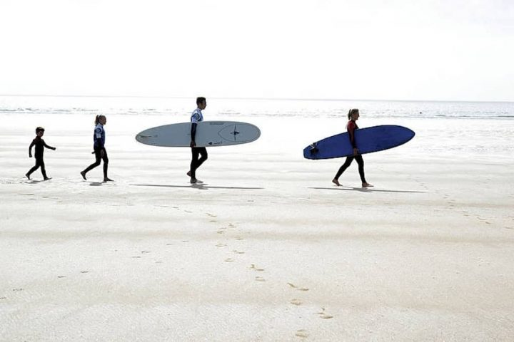 Family with surf boards walknig across beach with sea in background Saunton Sands Devon
