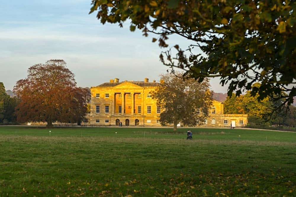 Basildon Park country house in autumn sunshine parkland and russet red trees