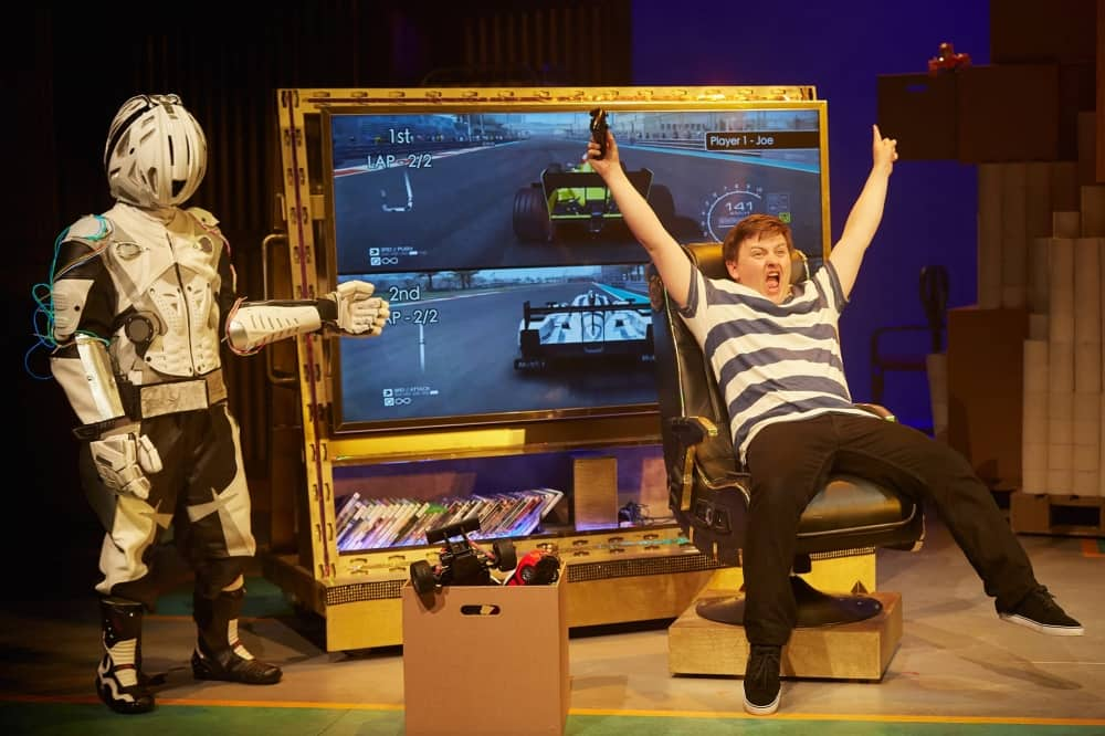 BillionaireBoyLiveOnStage boy giant tv screen playing comuter gsme with robot