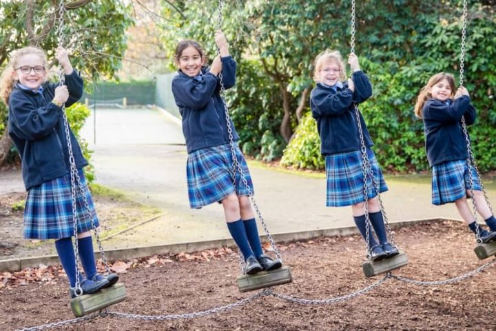 Coworth-Flexlands-chain-swing girls in blue tartan skirt and navy blazers on swing