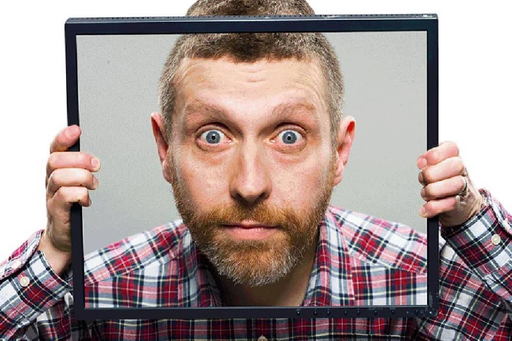 Dave Gorman comedian in check shirt holding close up image of his face up to his head