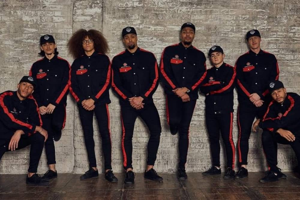 Diversity 2019 10th anniversary tour dance crew wearing black and red stripe tracksuits leaning against brick wall