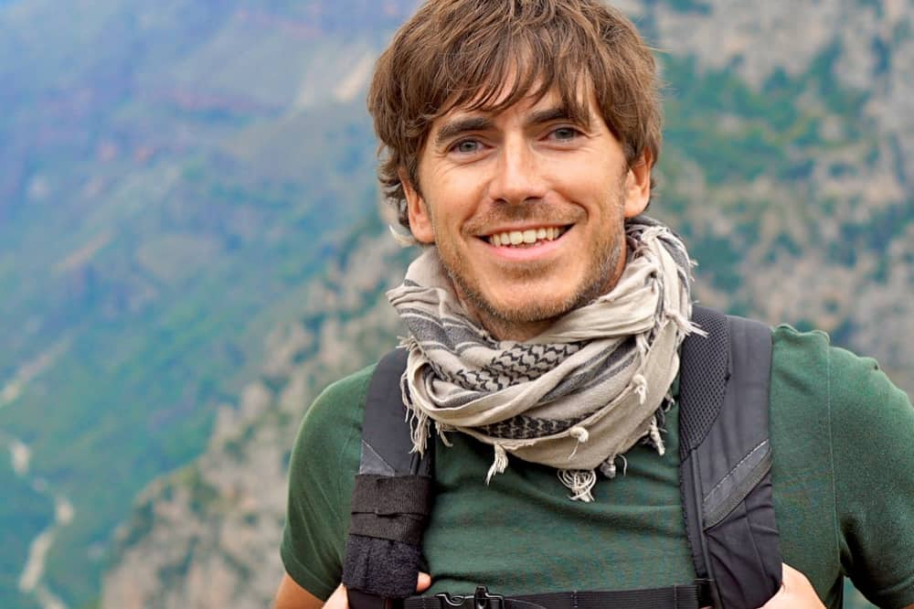 Explorer Simon Reeve man in green t short and scarf with mountai background