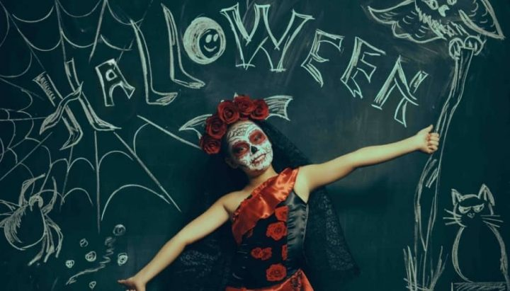 Girl day of the dead costumme and make up chalkboard wall with halloween writing