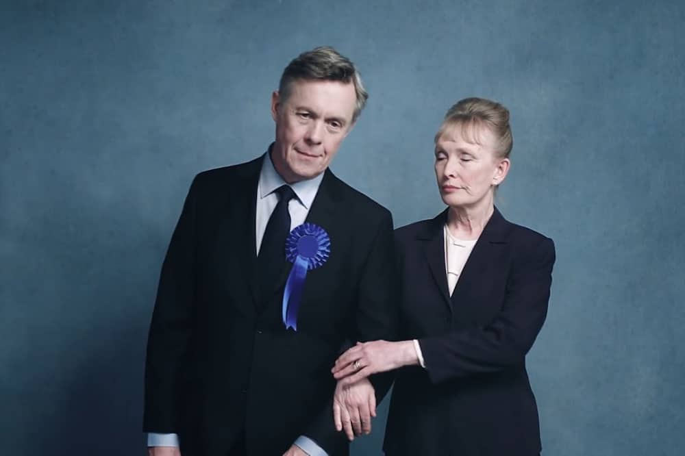 NT Live Hansard Tpry MP wearing suit and blue rosette with wife in blue suit