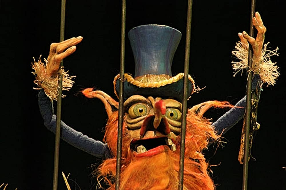 Rumpelstiltskin and the snail of destiny ginger bearded puppet behind bars wearing a top hat