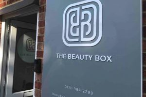 The Beauty Box Pangbourne entrance grey and white logo on wall