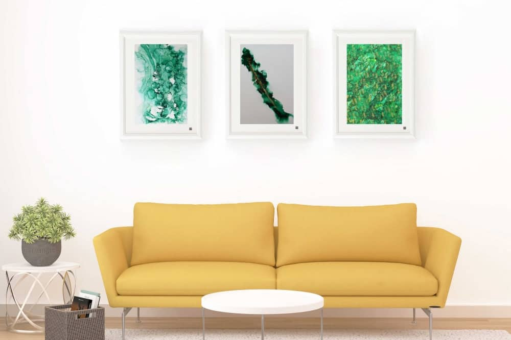 yellow sofa three green organic images on wall in white frames