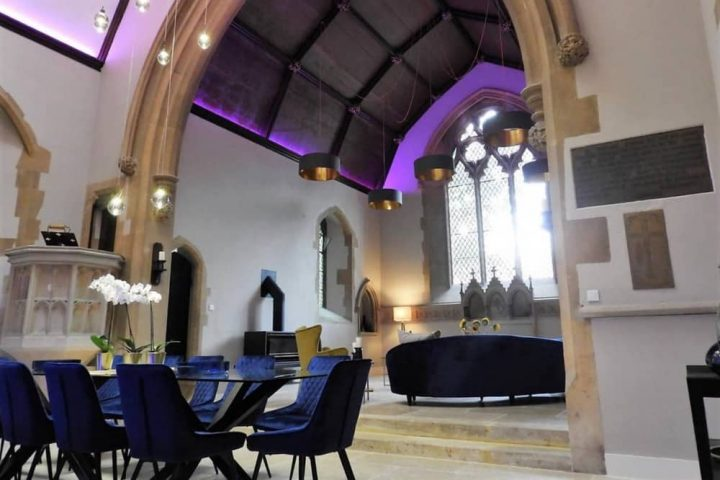 Church House Berkshrie main living room velvet curved sofas large hanging pendant lights stained glass windows and purple lighting