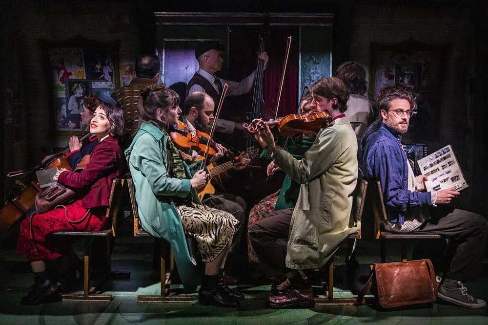 Amelie the musical in front of large fans and musicians playing violins