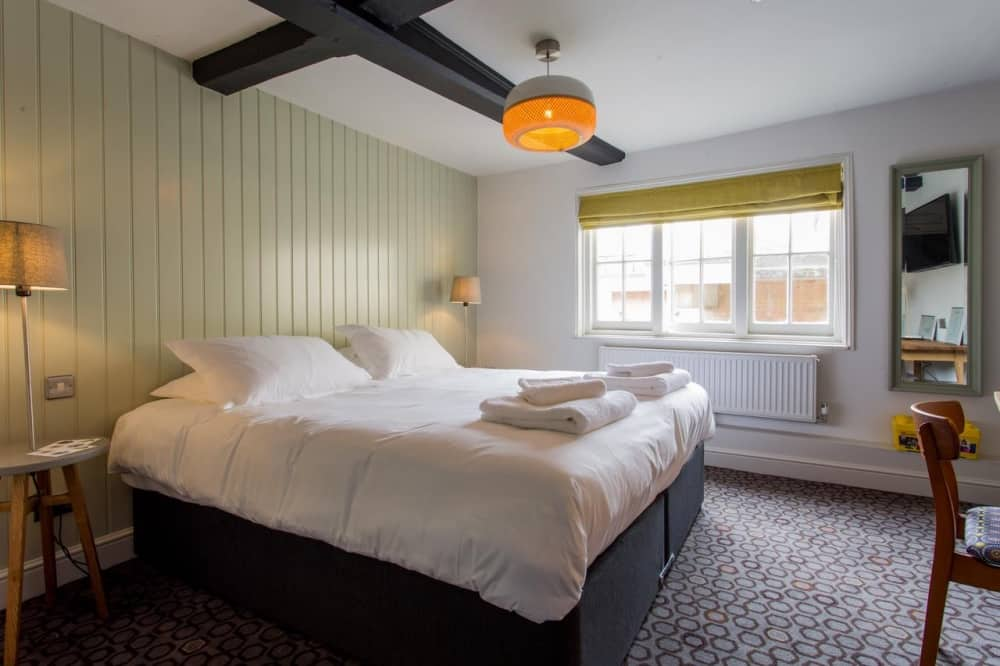 The Dolphin Newbury Berkshire rooms lime wooden T&G panelled wall retro light white bedlinen and patterned carpet