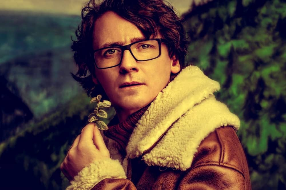 Comedian Ed Byrne leather and hearling flight jacket glasses holding foliage