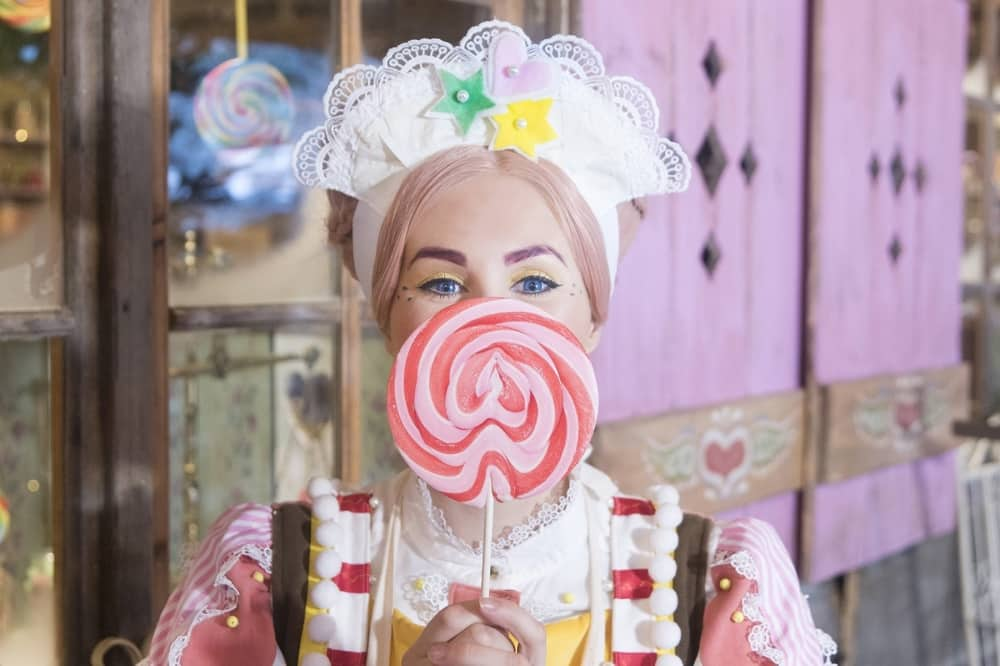 Lampland Uk Woman with large lollipop heald up to hger face